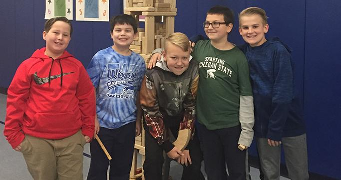 Wixom Prime Time Care students in front of a block tower they built.