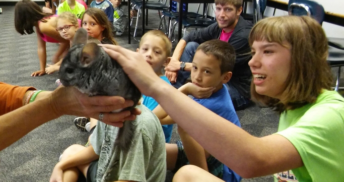 "Student petting animal during ""Animal Guy"" presentation"