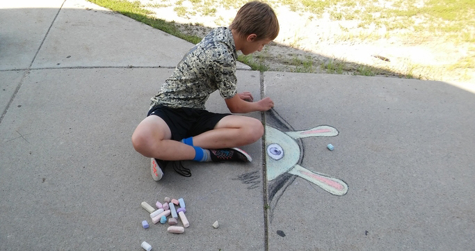 Student creating sidewalk chalk art