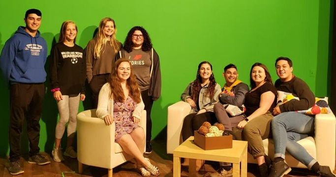 students sitting on a couch on a green screen film set